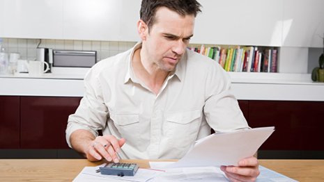 Disclaimer of Debt: Man using calculator while looking at paper