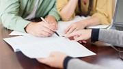 Assumed Names: Man signing on paper