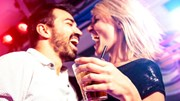 Deals on Tap: Man and Woman at bar drinking, looking happy